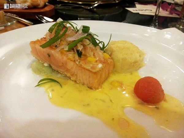 Slow-baked salmon fillet with pomelo mango kaffir lime salsa, saffron cream, and pomelo hollandaise